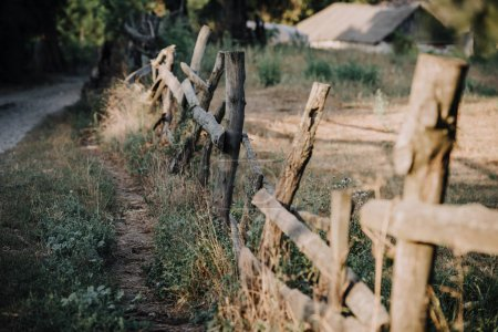 selective focus of wooden fence on meadow in countryside