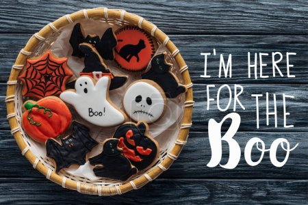 "top view of wicker basket with homemade spooky halloween cookies on wooden table  with ""Im here for the Boo"" lettering"