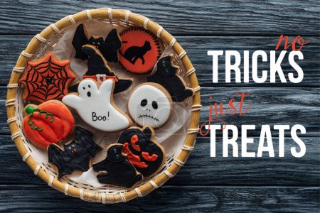 """top view of wicker basket with homemade spooky halloween cookies on wooden table  with """"no tricks just treats"""" lettering"""
