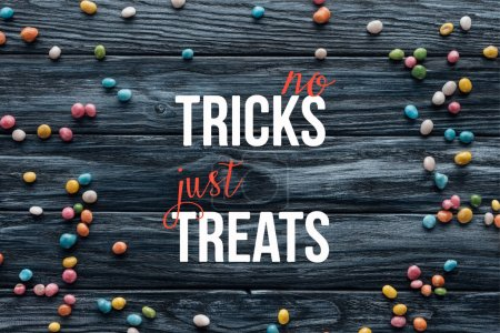 "elevated view of arranged colorful delicious candies on wooden background  with ""no tricks just treats"" lettering"