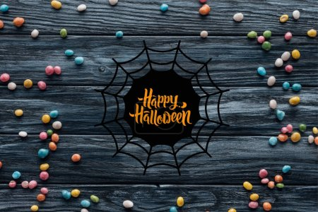 "elevated view of arranged colorful delicious candies on wooden background with spider web and ""happy halloween"" lettering"