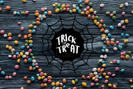 "circle made of colorful delicious candies on wooden background with spider web and ""trick or treat"" lettering"
