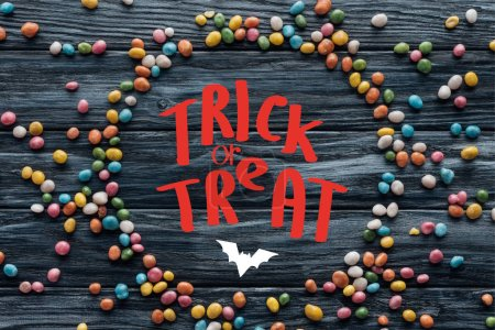 "circle made of colorful delicious candies on wooden background with bat and ""trick or treat"" lettering"