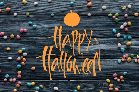 """elevated view of arranged colorful delicious candies on wooden background with pumpkin and """"happy halloween"""" lettering"""