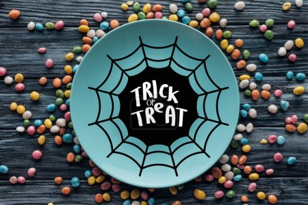 """top view of plate with spider web and """"trick or treat"""" lettering surrounded by colorful candies on wooden table"""