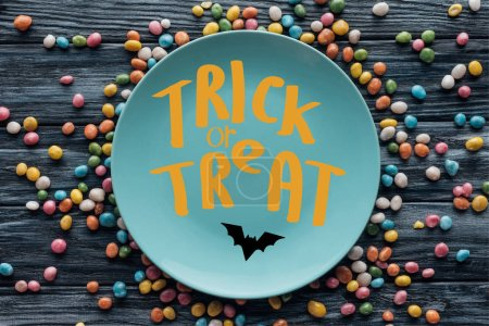 "top view of plate with bat and ""trick or treat"" lettering surrounded by colorful candies on wooden table"