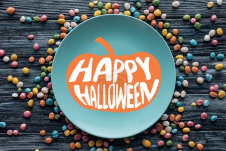 "top view of plate with pumpkin and ""happy halloween"" lettering surrounded by colorful candies on wooden table"