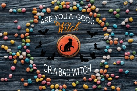 "elevated view of composition with homemade halloween cookie surrounded by colorful candies on wooden table with ""are you a good witch or a bad witch"" lettering"