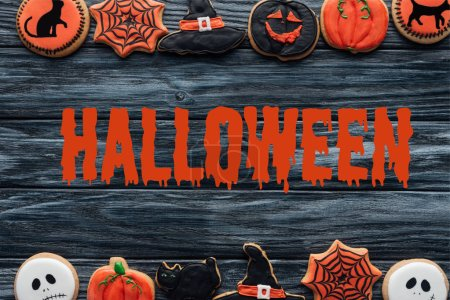 "top view of arranged homemade cookies placed in rows on wooden background  with ""halloween"" lettering"