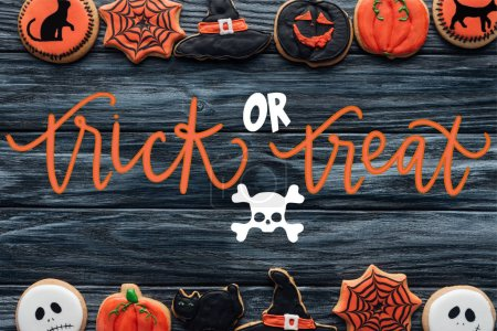 """top view of arranged halloween homemade cookies placed in rows on wooden background with skull and """"trick or treat"""" lettering"""