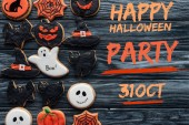 """elevated view of spooky delicious halloween cookies placed in rows on wooden background  with """"happy halloween party, 31 october"""" lettering"""
