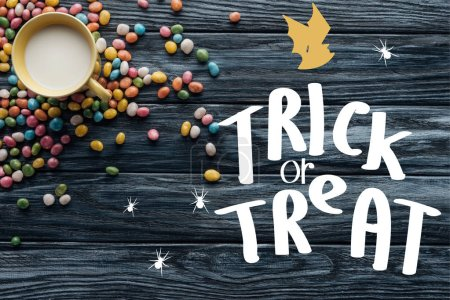 """elevated view of colorful candies and cup with milk on wooden background  with bat and """"trick or treat"""" lettering"""