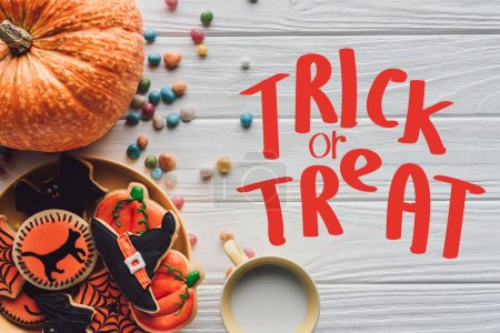 "top view of pumpkin, plate with halloween cookies, candies and cup with milk on wooden table  with ""trick or treat"" lettering"