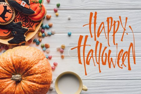 """elevated view of pumpkin, plate with halloween cookies, candies and cup with milk on wooden background  with """"happy halloween"""" lettering"""