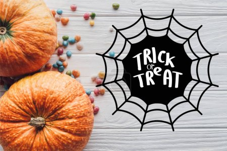 """top view of pumpkins and colorful candies on wooden background with spider web and """"trick or treat"""" lettering"""