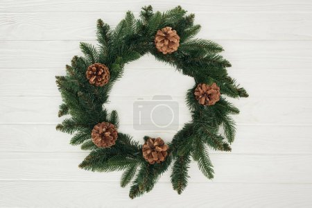 close-up view of beautiful christmas wreath with pine cones on white wooden background