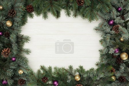 top view of beautiful evergreen fir twigs with shiny baubles and pine cones on white wooden background