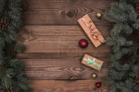 top view of christmas presents, shiny baubles and coniferous branches with pine cones on wooden background
