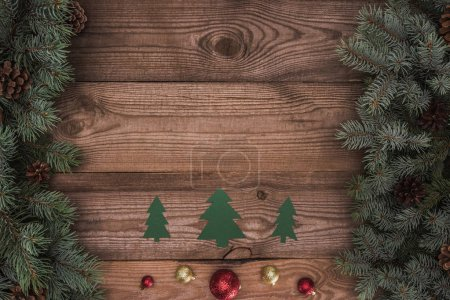 top view of green paper fir trees with shiny baubles and coniferous branches with pine cones on wooden surface, christmas background