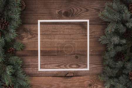 top view of white frame and evergreen twigs with pine cones on wooden background
