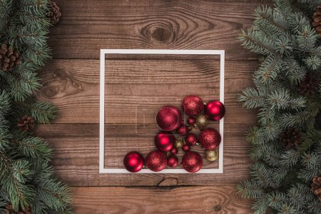 top view of white frame, shiny red and golden balls and coniferous branches with pine cones, christmas background