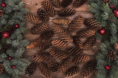 top view of brown pine cones with fir twigs and red baubles on wooden background
