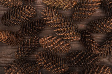 top view of brown pine cones on wooden background