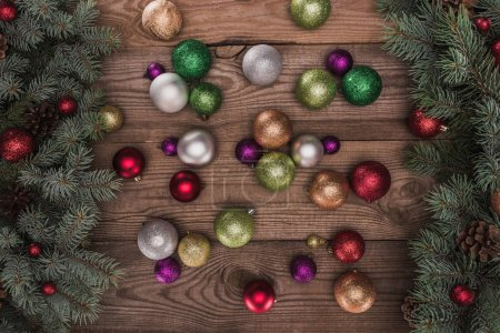 top view of shiny colorful baubles and christmas tree branches on wooden background