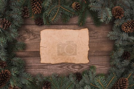 Photo for Top view of blank parchment and coniferous branches with pine cones on wooden background - Royalty Free Image