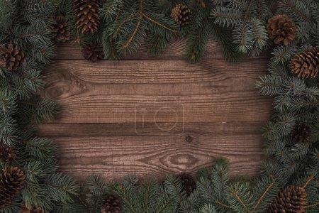 Photo pour Vue de dessus de belles branches de conifères à feuilles persistantes et des pommes de pin sur fond en bois - image libre de droit