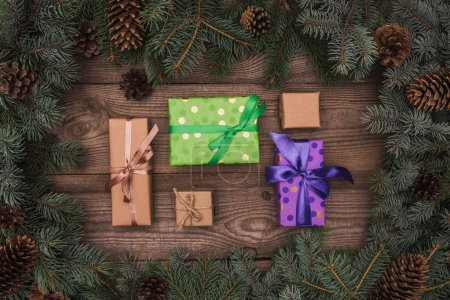 top view of wrapped christmas presents and coniferous branches with pine cones on wooden background