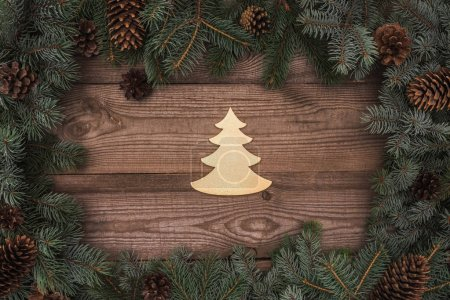 top view of beautiful christmas tree symbol and coniferous branches with pine cones on wooden background