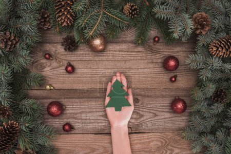cropped shot of person holding christmas tree symbol above wooden surface with coniferous branches, pine cones and shiny baubles