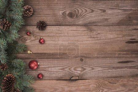 Photo pour Vue de dessus des boules brillantes, des brindilles de conifères et des cônes de pin sur fond en bois - image libre de droit