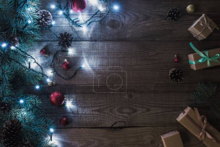 christmas presents, shiny baubles and fir twigs with illuminated garland on wooden background