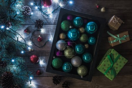 top view of christmas presents, shiny baubles and fir twigs with illuminated garland on wooden background