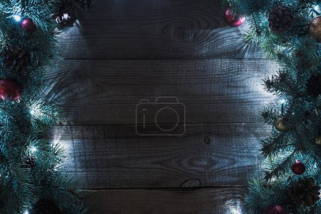 top view of christmas tree twigs with pine cones, baubles and illuminated garland on wooden background