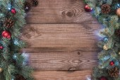 beautiful christmas tree branches with baubles, pine cones and illuminated garland on wooden background