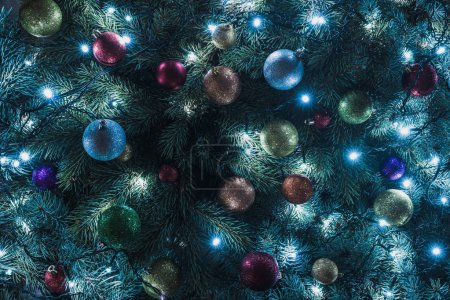 close-up view of beautiful christmas tree with colorful balls and illuminated garland