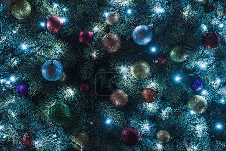 Photo pour Vue rapprochée du magnifique sapin de Noël avec boules colorées et guirlande illuminée - image libre de droit