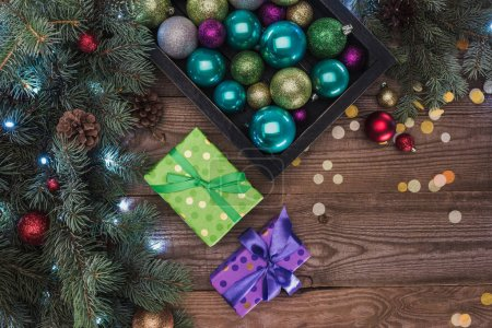top view of beautiful colorful shiny baubles, gift boxes and fir twigs on wooden background