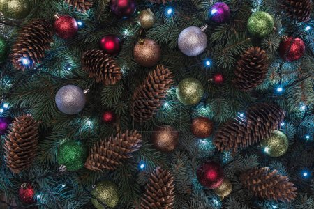 close-up view of beautiful christmas tree with pine cones, colorful balls and illuminated garland