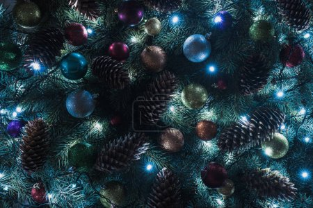 close-up view of beautiful christmas tree with pine cones, colorful baubles and illuminated garland