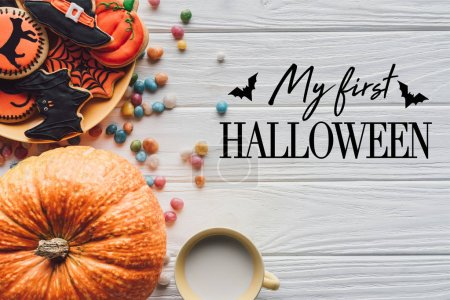 """elevated view of pumpkin, plate with halloween cookies, candies and cup with milk on wooden background with bats and """"my first halloween"""" lettering"""
