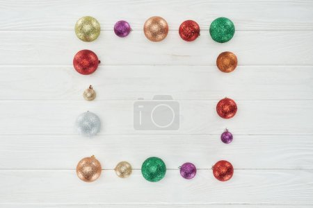 top view of shiny colorful christmas balls on white wooden background