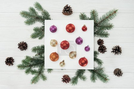 top view of shiny colorful christmas balls on white card, fir twigs and pine cones on wooden surface