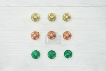 top view of beautiful shiny christmas balls on white wooden surface