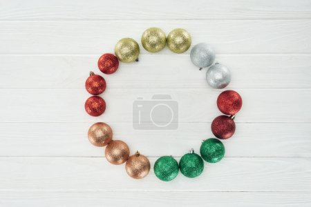 top view of round frame made of beautiful shiny colorful christmas balls on white wooden surface