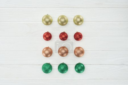 top view of beautiful shiny colorful christmas balls on white wooden surface