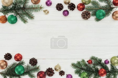 top view of colorful shiny christmas balls, fir twigs and pine cones on white wooden background